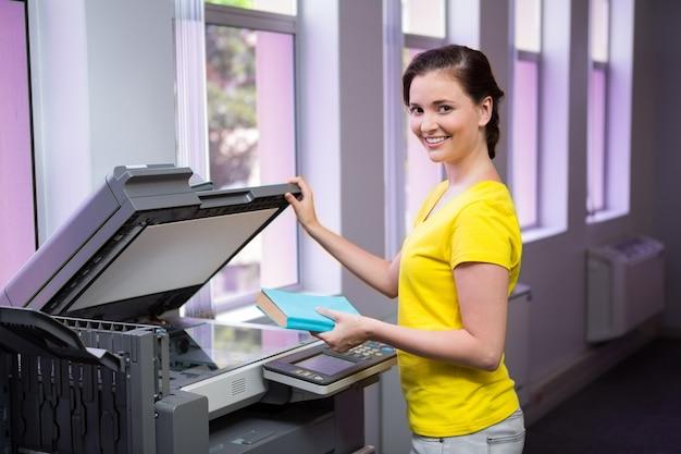 Une étudiante photocopie son livre à la bibliothèque