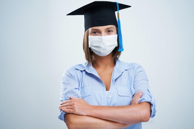 Étudiante portant un masque de protection isolé sur fond blanc