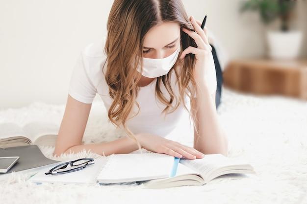 Étudiante portant un masque de protection médicale se trouve sur un canapé avec des livres, des cahiers, un cahier et fait ses devoirs, l'enseignement à distance, l'enseignement à domicile, le coronovirus, la quarantaine