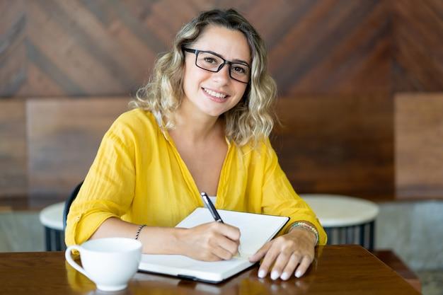 Étudiante positive dans des verres à faire leurs devoirs
