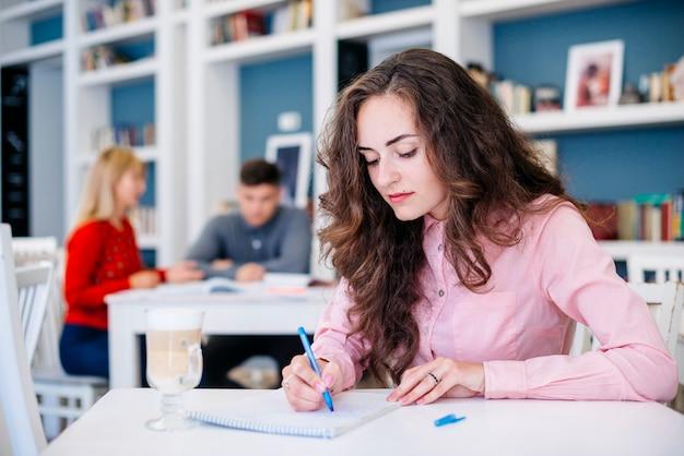 Étudiante, prendre des notes dans le bloc-notes
