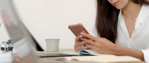 Étudiante prendre une pause avec un smartphone tout en faisant une tâche avec un ordinateur portable et de la papeterie sur table
