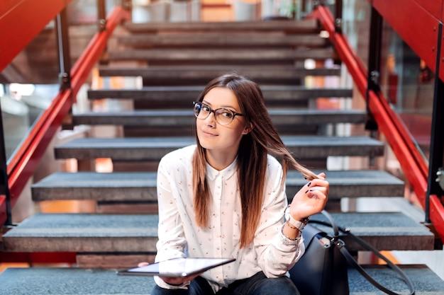 Étudiante de race blanche avec des lunettes touchant ses cheveux et tenant la tablette tout en étant assis dans les escaliers à l'intérieur du collage.