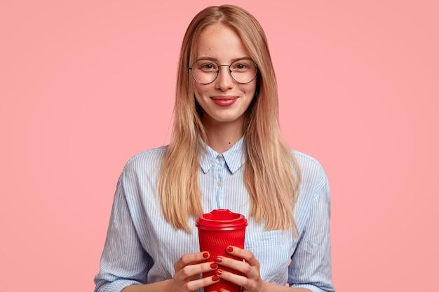 Une étudiante à la recherche agréable a une pause-café, détient une tasse rouge à emporter, porte des lunettes rondes et une chemise