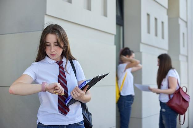 Une étudiante regarde la montre-bracelet, l'enseignement universitaire, les étudiants adolescents en plein air.