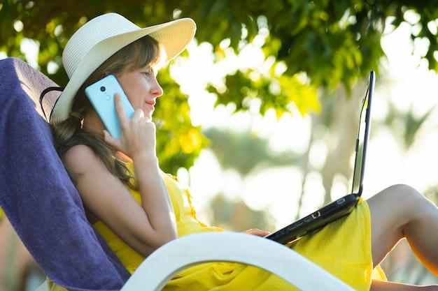 Étudiante en robe d'été jaune reposant sur la pelouse verte dans le parc d'été étudie sur ordinateur portable ayant une conversation sur téléphone mobile.