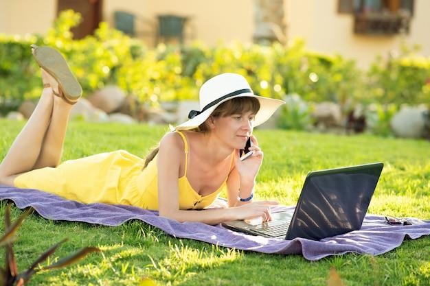 Étudiante en robe d'été jaune reposant sur la pelouse verte étudie sur ordinateur portable ayant une conversation sur téléphone mobile.