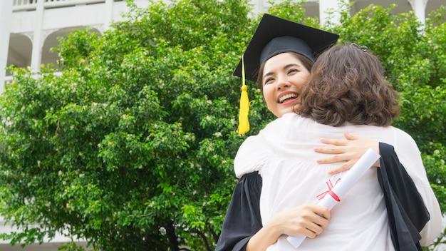 Étudiante avec les robes de graduation et un chapeau embrassent le parent