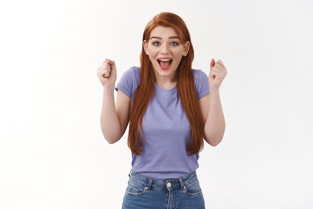 Une étudiante rousse joyeuse et enthousiaste acclamant l'équipe du collège, s'enracinant pour un ami, serrant les poings étonnés, souriant joyeusement, regardant l'avant fasciné, triomphant, célébrant la victoire