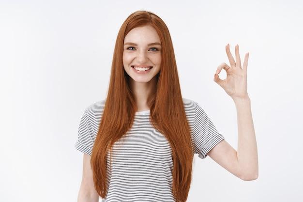 Une étudiante rousse séduisante et ravie donne une réponse positive montre d'accord ok geste normal exprime une bonne attitude positive comme résultat, mur blanc debout
