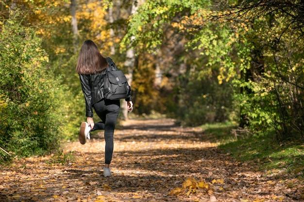 Une étudiante se promène dans le parc en automne. fille aux cheveux noirs redresse ses chaussures. promenade solitaire à travers les bois. vue arrière.