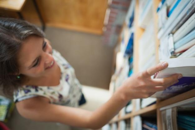 Étudiante en sélectionnant le livre dans la bibliothèque