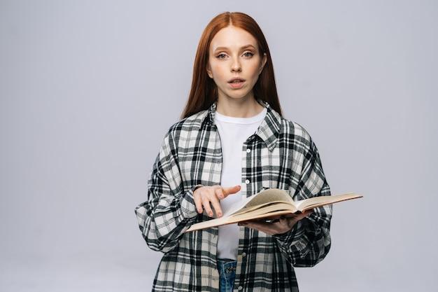Étudiante sérieuse de jeune femme tournant des pages de livre tout en lisant