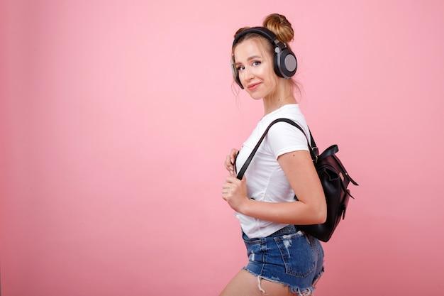 Étudiante sexy dans les écouteurs et avec un sac à dos sur un espace rose