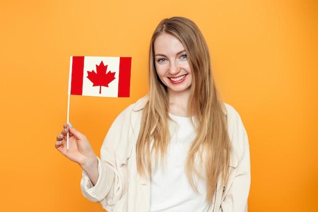Étudiante souriant et tenant un petit drapeau canada