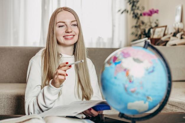 Étudiante souriante étudie la géographie sur un globe