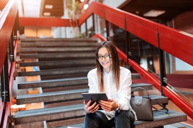 Étudiante souriante avec des lunettes et des cheveux bruns à l'aide d'une tablette tout en étant assis dans les escaliers.