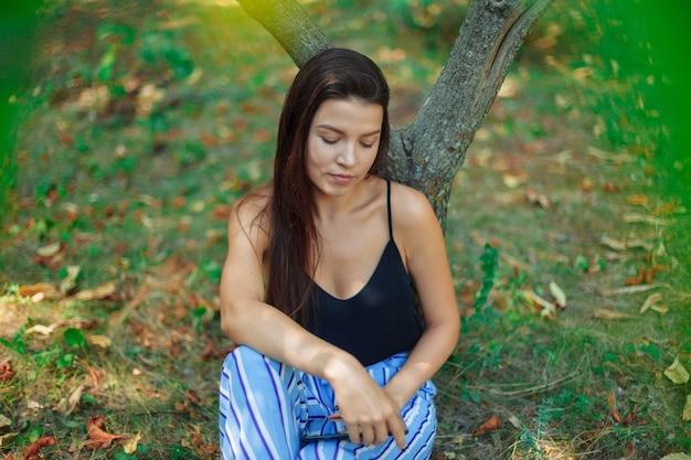 Étudiante sous l'arbre est assis avec une tablette. la formation en ligne.