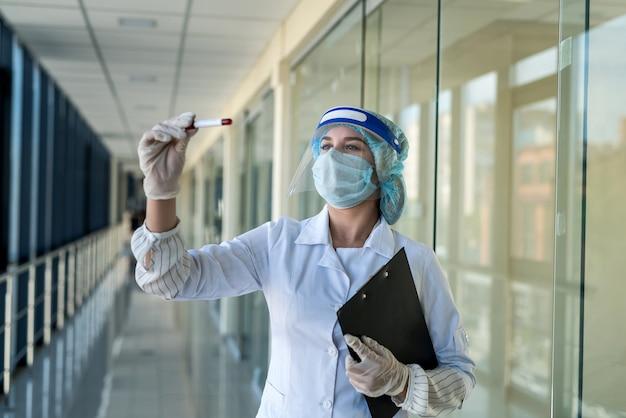 Une étudiante stagiaire regarde un tube à essai de sang en laboratoire pour déterminer le virus coronavirus. covid 19