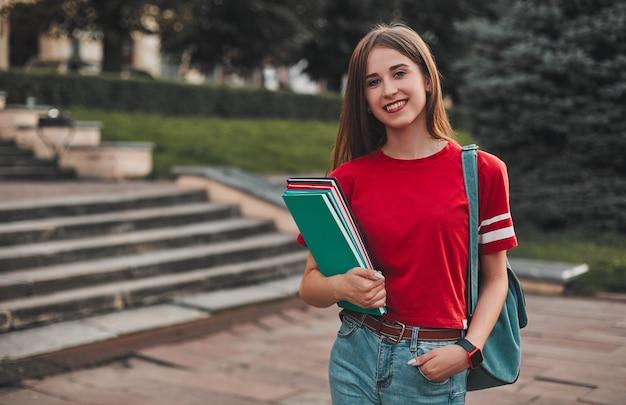 Une étudiante en t-shirt rouge avec un sac à dos et des cahiers de couleur, tenant sa main dans sa poche et souriant