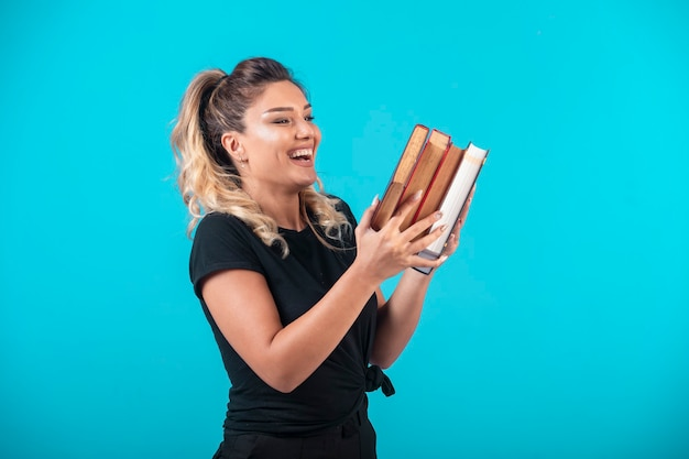 Étudiante tenant un gros stock de livres et se sent positif