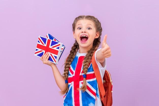 Une étudiante, tenant des livres sur l'apprentissage de l'anglais dans ses mains et souriante, montre son pouce vers le haut. fond isolé.