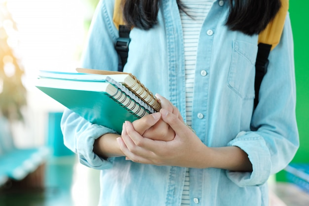 Étudiante tenant des livres et porter un sac d'école tout en marchant dans le fond du campus de l'école
