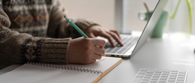 Étudiante universitaire en ligne avec ordinateur portable et papeterie sur la table de travail à la maison
