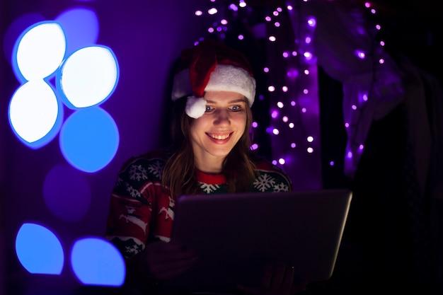 Étudiante en vêtements de noël est assise à la maison avec un ordinateur portable la nuit
