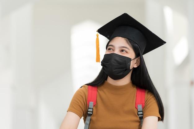 Les étudiantes, les diplômées universitaires, portent des chapeaux noirs, des pompons jaunes et portent des masques pendant l'épidémie.