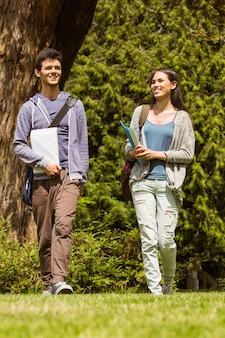Étudiants amis marchant avec sac à bandoulière et tenant le bloc-notes
