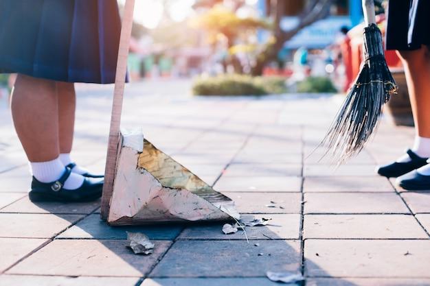 Étudiants asiatiques fille uniforme balayant les feuilles séchées sur le sol à l'école.
