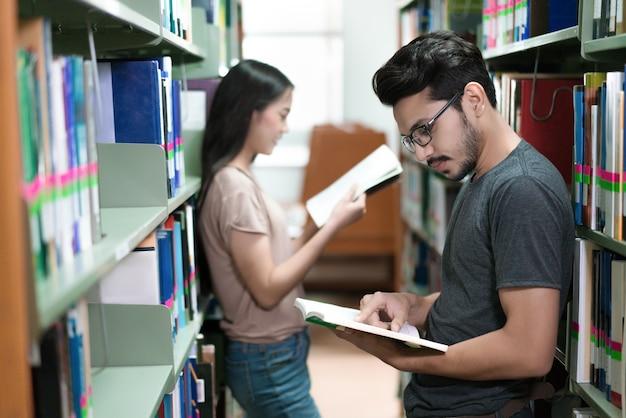 Étudiants asiatiques lecture aux étagères