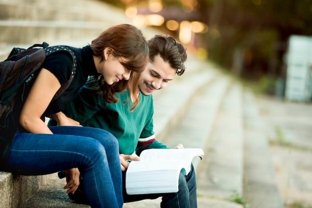 Les étudiants asiatiques lisent à l'extérieur. ils se préparent aux examens.