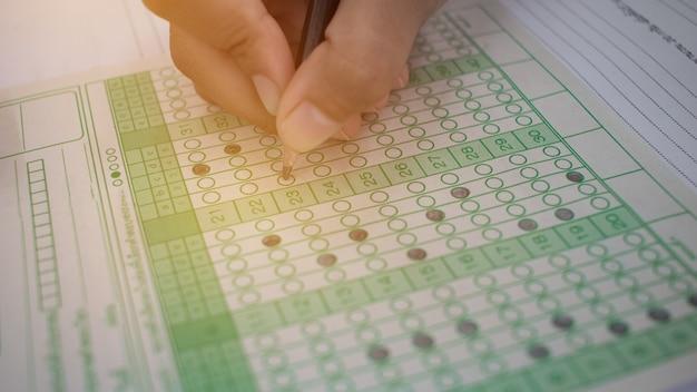 Étudiants asiatiques tenant un crayon dans la main faisant des quiz à choix multiples