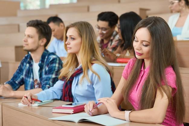 Des étudiants assis sur des bureaux en bois dans une salle de classe universitaire moderne.