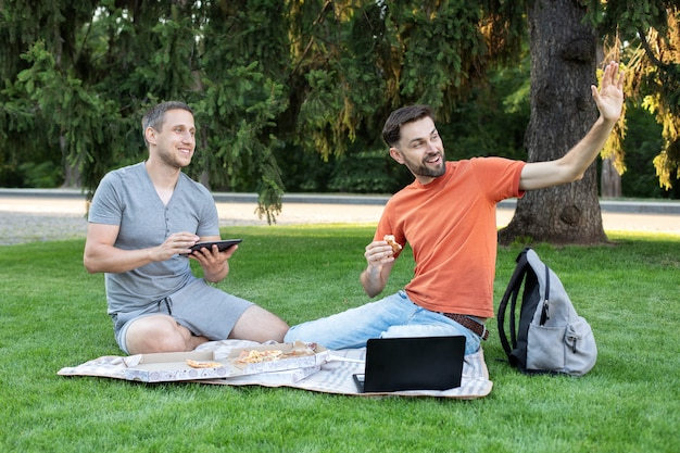 Les étudiants assis avec dans le parc de la ville à l'aide d'un ordinateur portable travaillant à l'extérieur montrant bonjour le geste. heureux jeune homme souriant et saluant des amis. étudiants qui étudient au parc et souriant. amitié, étudier,