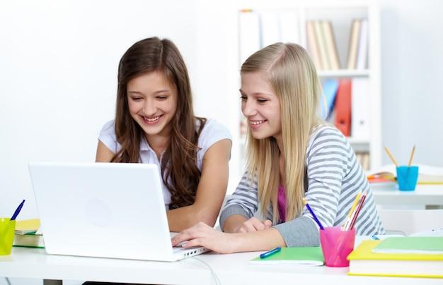 Les étudiants ayant du plaisir avec un ordinateur portable