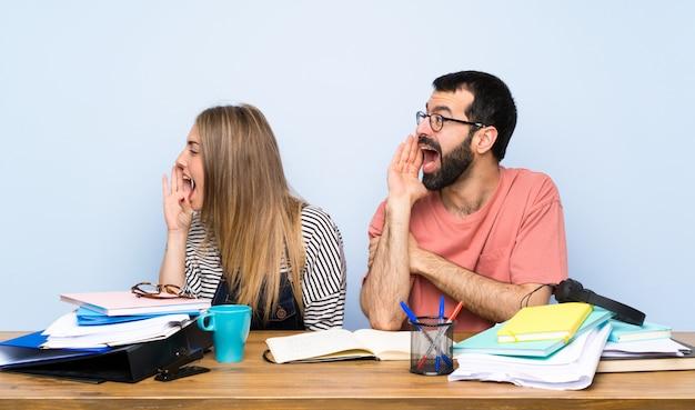 Étudiants avec beaucoup de livres criant avec la bouche grande ouverte sur le côté