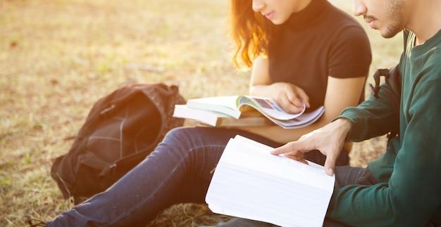 Les étudiants consultant cours pour les examens ils se sont assis à l'extérieur de l'herbe