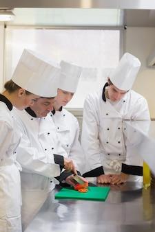 Des étudiants culinaires apprennent à couper des légumes