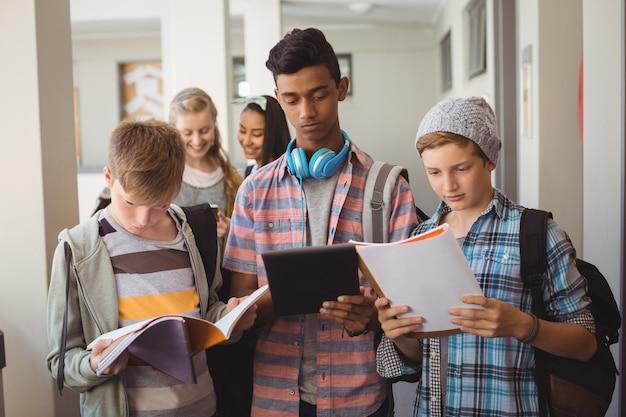 Étudiants debout avec ordinateur portable et tablette numérique dans le couloir
