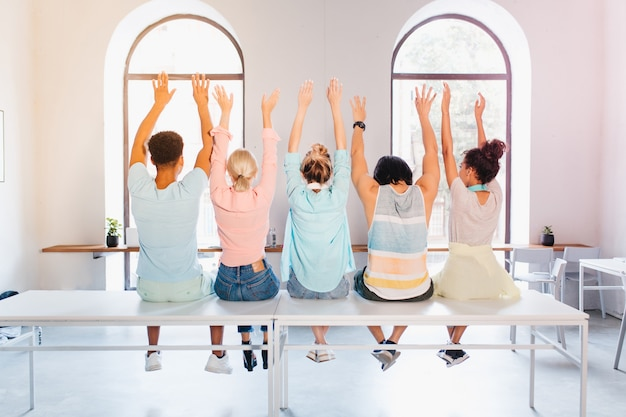 Étudiants drôles posant avec les mains pour l'album photo avant d'obtenir leur diplôme. photo intérieure de l'arrière de personnes assises devant une grande fenêtre dans un appartement lumineux.