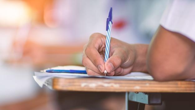 Étudiants écrivant et lisant des exercices de feuilles de réponses aux examens en classe d'école avec stress