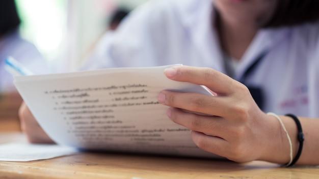 Étudiants écrivant et lisant des exercices de feuilles de réponses aux examens en classe de l'école avec stress