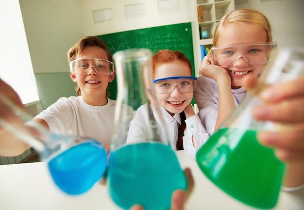 Étudiants enthousiaste détenant des flacons avec des liquides