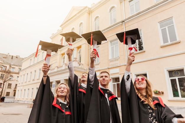 Étudiants à faible angle détenant un diplôme