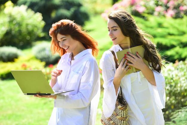 Étudiants filles heureuses jeunes étudiantes avec des cahiers dans un parc étudiant au collège