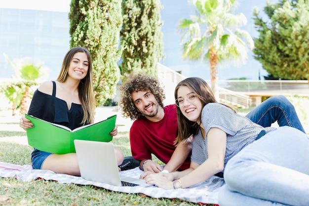 Étudiants gais avec manuel et ordinateur portable moderne