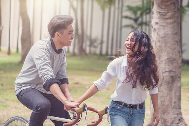 Étudiants heureux couple avec bicyclettes sur le parc du campus